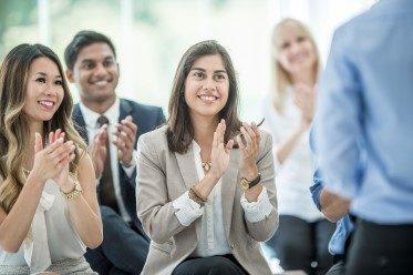 kvinna klappar efter kurs om Kommunikativt Ledarskap