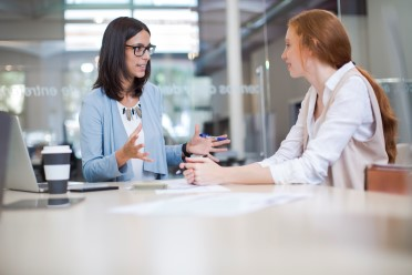 två kollegor som har intern kommunikation och delar medarbetarskap inom företaget